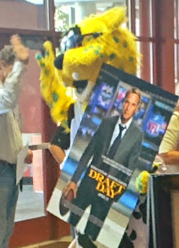 Jaguars mascot Jaxon de Ville greets guests holding a Draft Day movie poster